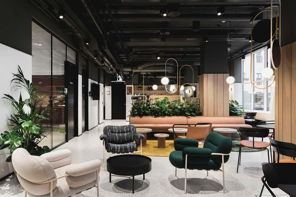 Une cafétéria d'entreprise confortable avec des fauteuils, des banquettes, de la verdure et une grande baie vitrée