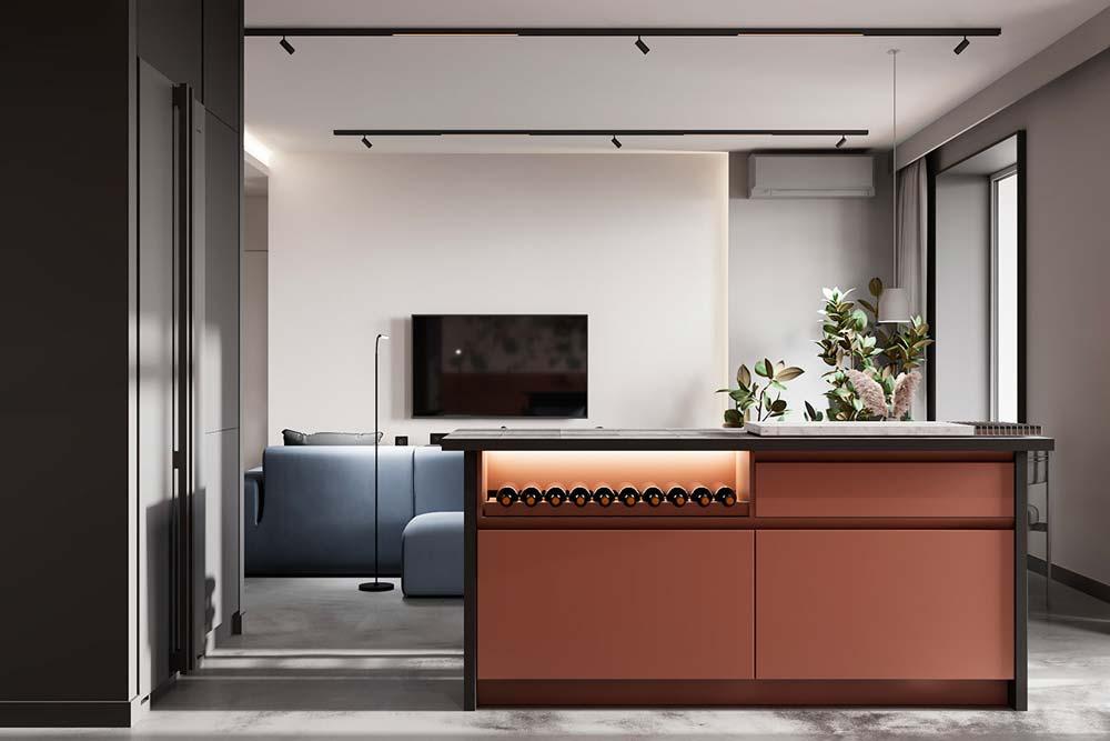 Une cuisine moderne avec un îlot central rose poudré pour ranger les bouteilles de vin