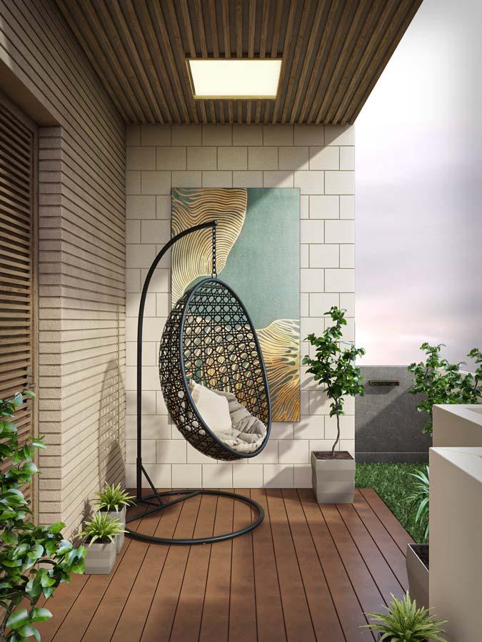 Un fauteuil en osier noir suspendu sur un balcon-terrasse en bois avec un coin de gazon synthétique
