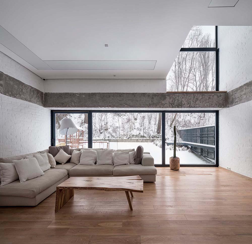 Un salon slow design avec parquet, table basse en bois et un grand canapé d'angle beige