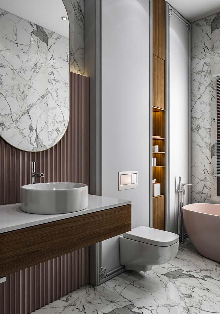 Une salle de bain en marbre blanc au mur en bois ondulé avec une baignoire rose