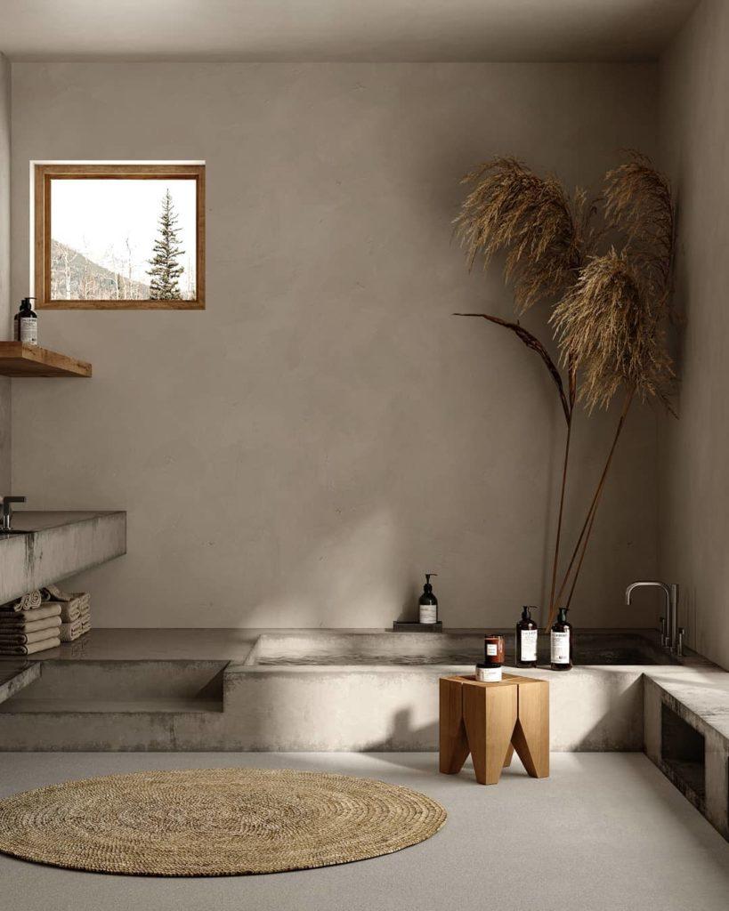 Une salle de bain slow design avec baignoire en pierre, tapis rond, herbes de la pampa et couleurs douces et neutres