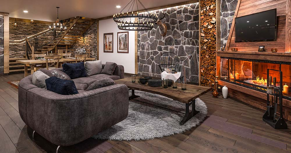 Un salon campagne chic chaleureux avec des murs en pierre et en bois, un plancher, une grande cheminée et une table basse en bois brut