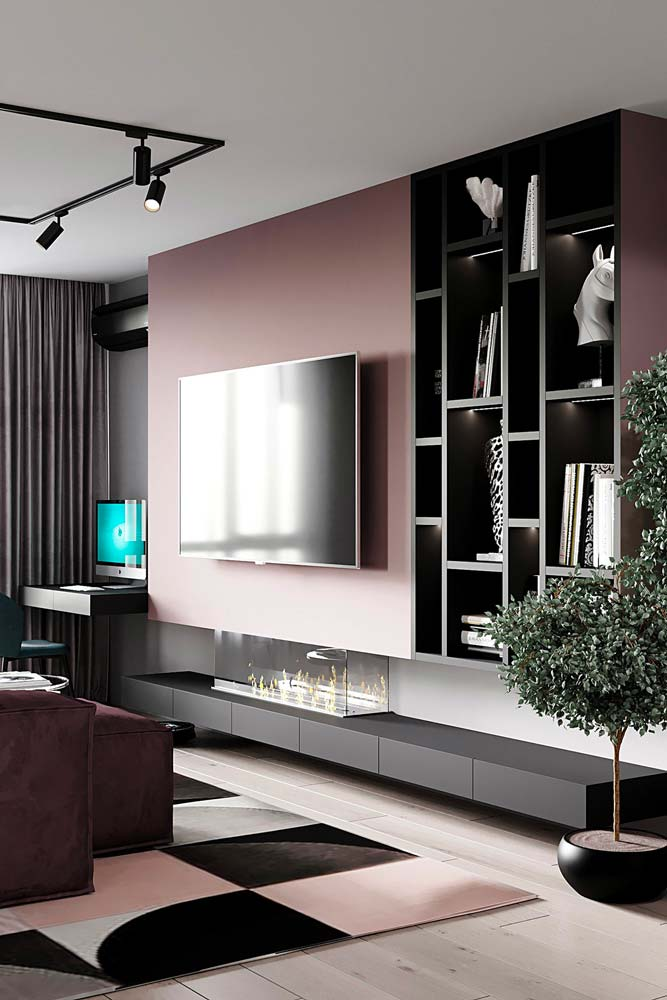 Un salon dynamique aux étagères noires, mur vieux rose et tapis en damier rose et noir