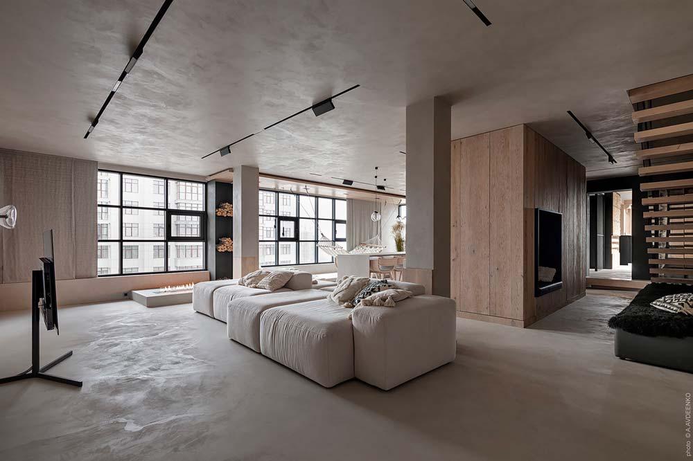 Un salon épuré et minimaliste en béton ciré avec un grand canapé central et des murs en lambris clair