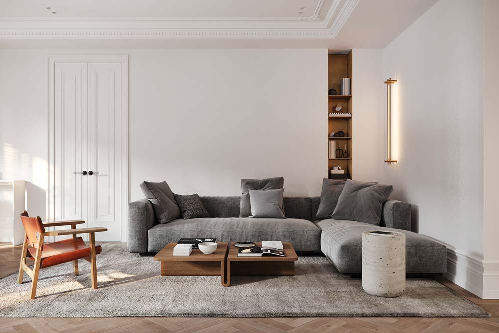 Un salon slow living avec un épais tapis, un canapé d'angle gris et des accessoires en bois noble