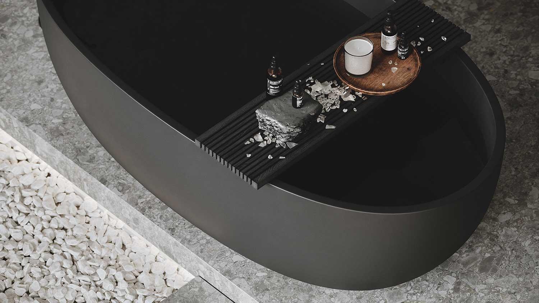 Une baignoire noire mate avec une planche de produits de soins sur une plateforme en terrazzo gris