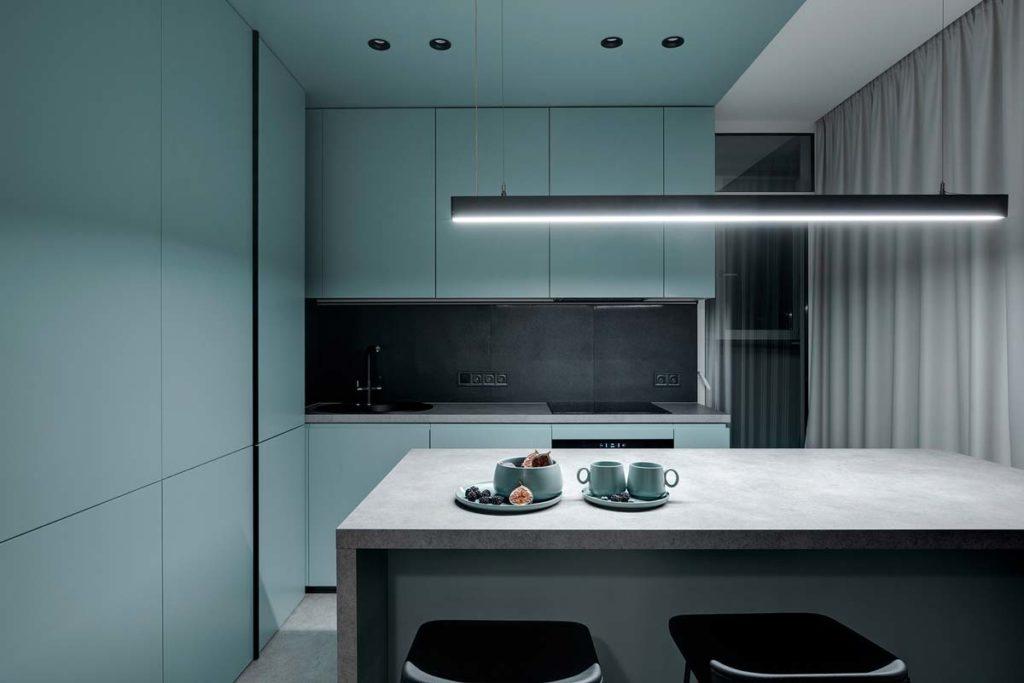 Une cuisine minimaliste avec des murs et des placards en blue sky et une table centrale grise