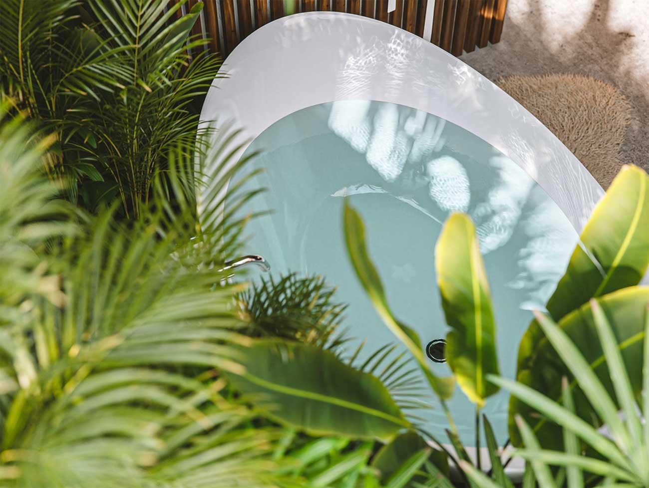 Une grande baignoire blanche avec des palmiers intérieurs