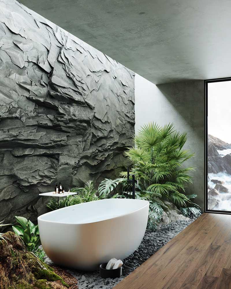 Une salle de bain avec un parquet en bois, un mur de pierre gris, une baignoire blanche et une décoration naturelle avec de la végétation