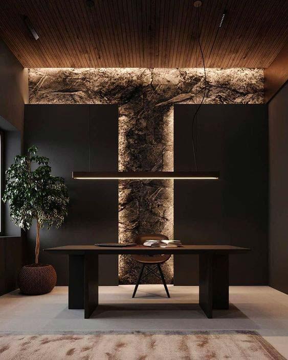 Un bureau de travail avec un mur en pierre, un plafond en bardage intérieur et un bureau en bois noble