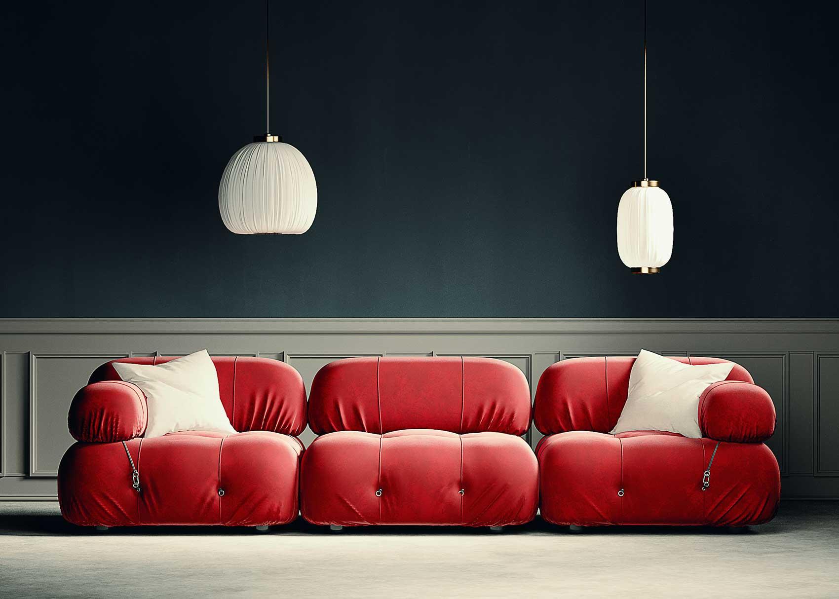 Un canapé modulable rouge dans un salon aux murs bleu pétrole et blanc avec des moulures