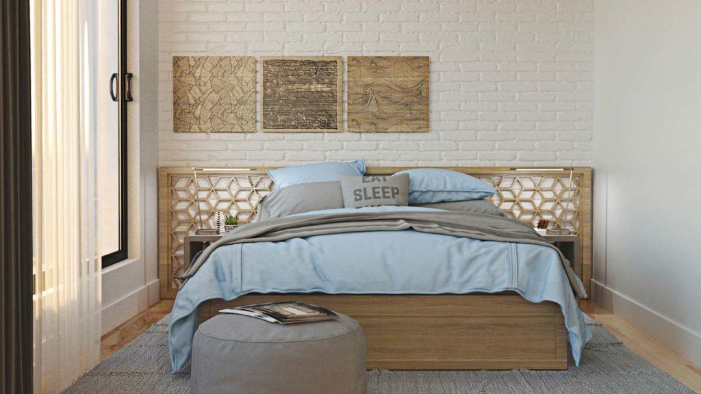 Une chambre avec un mur en pierres peint en blanc, un grand tapis gris et un lit double paré de linge de lit gris et blue sky