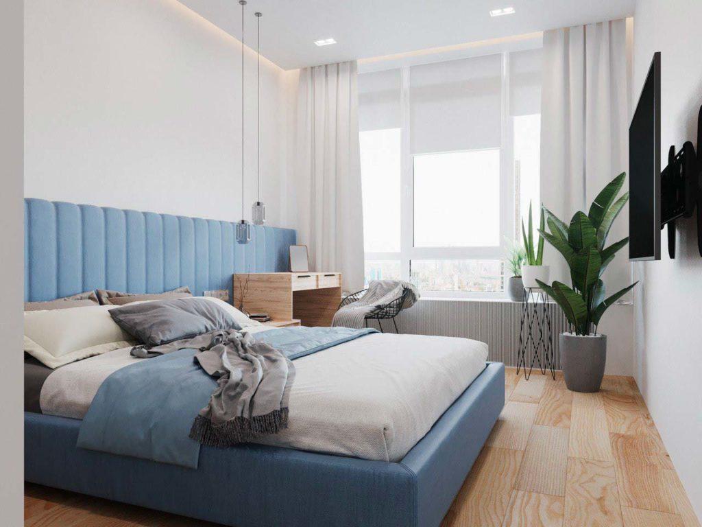 Chambre avec un plancher en bois blond et une tête de lit en velours blue sky