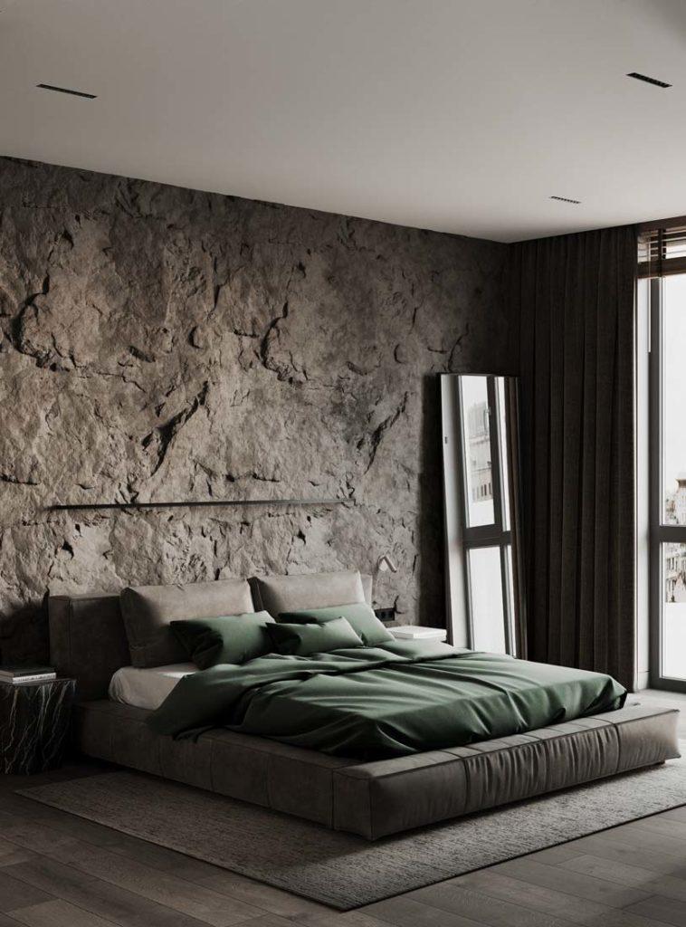 Une chambre zen grise et kaki avec un mur tête de lit en pierre, miroir et grande fenêtre lumineuse