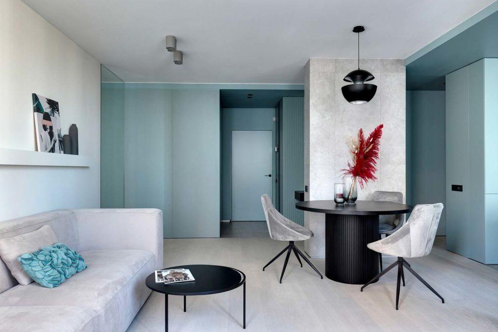 Un coin salon aux murs blancs et blue sky avec du mobilier noir et gris et un canapé en velours blanc
