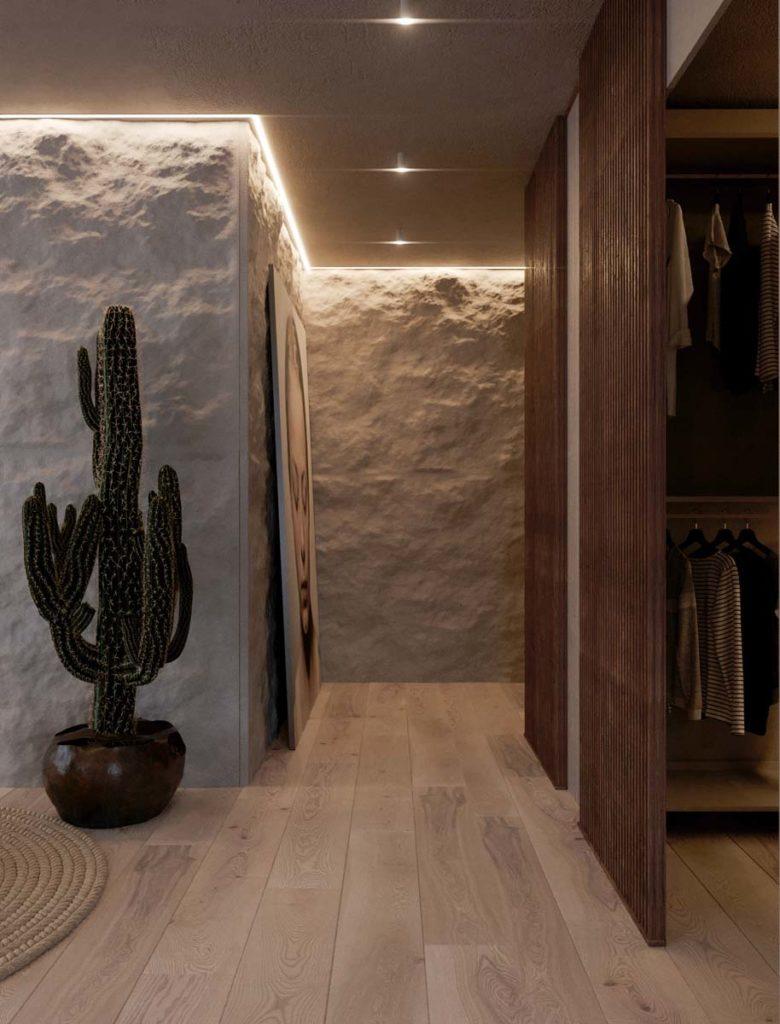 Un couloir en pierre éclairé par des néons avec de la déco zen et un plancher en bois clair