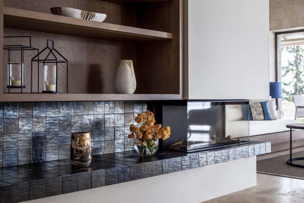 Une crédence en zellige bleu nacré dans une cuisine avec des étagères hautes en bois