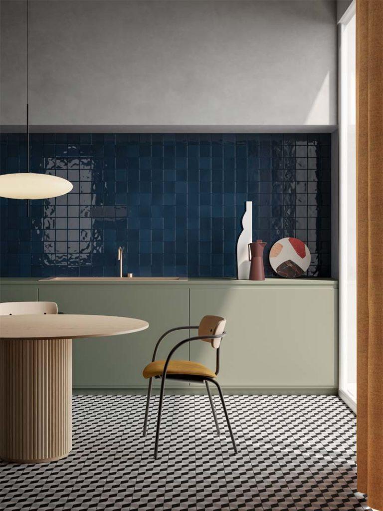 Une crédence bleu roi dans une cuisine avec un sol en damier noir et blanc