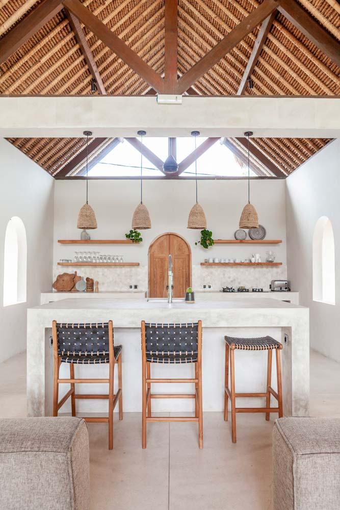 Une cuisine avec une grande charpente en bois et un îlot central blanc faisant office de bar