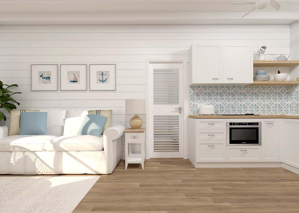 Cuisine et salon style bord de mer avec du lambris blanc au mur et couleur bois au sol, des meubles blanc et un canapé blanc aux coussins bleus