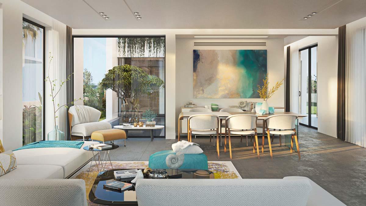 Un salon avec un grand canapé d'angle, une salle à manger avec du mobilier blanc et de la petite déco en fossiles d'ammonites