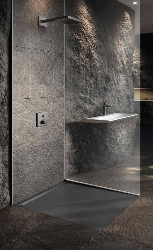Des couleurs grises et un mur en pierre dans une salle de bain, à côté d'une cabine de douche