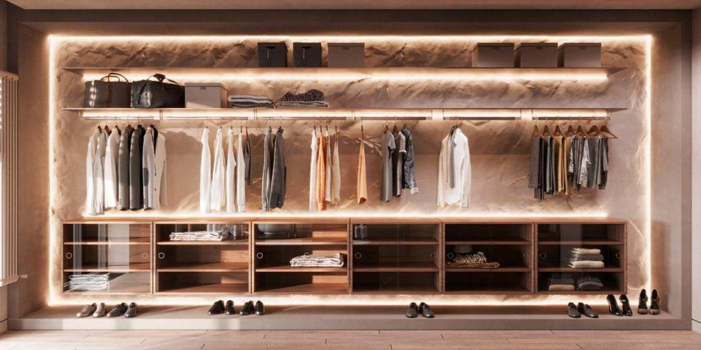 Un grand dressing sur un mur de pierre claire avec des étagères éclairées et des rangements en essences de bois assorties