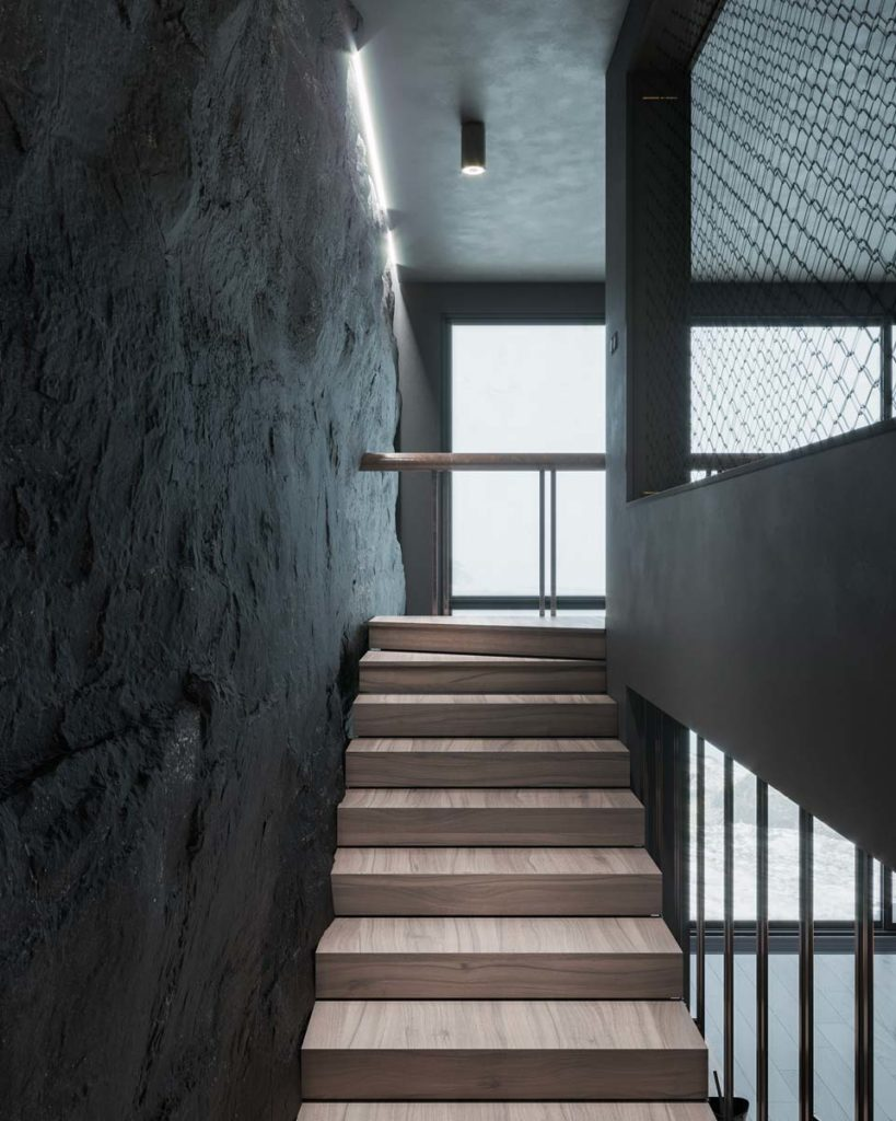 Des escaliers étroits contre un mur de pierre gris sombre face à une grande fenêtre