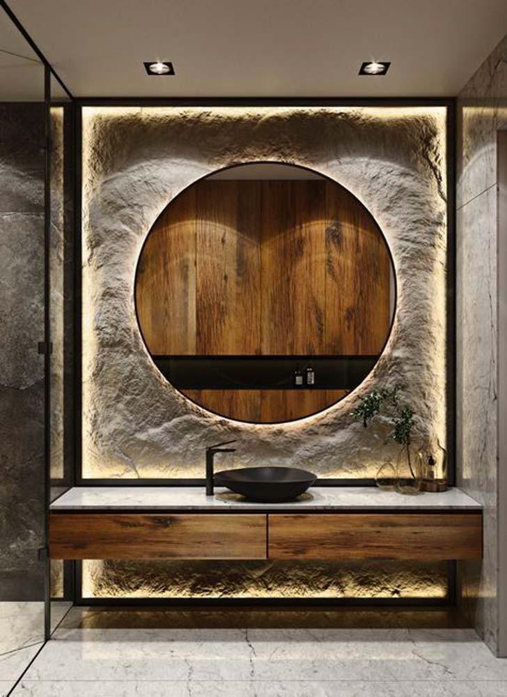 Salle de bain avec mur de pierre derrière un grand miroir rond éclairé par des néons et sol en carrelage blanc