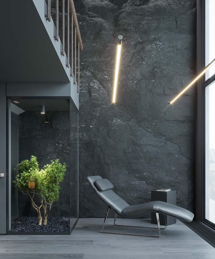 Un coin détente près d'un haut mur de pierre grise avec un balcon intérieur, un fauteuil relaxant et une plante verte sous verrière