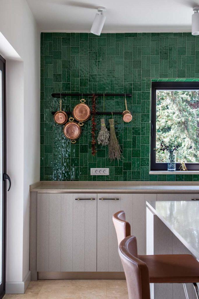 Un mur de cuisine en zellige vert avec des casseroles en cuivre et des meubles en bois blond