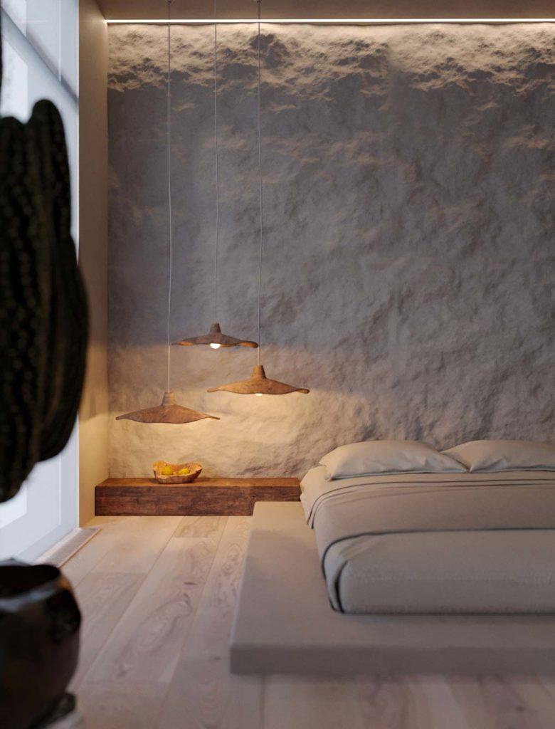 Une chambre confortable et douillette avec un mur de pierre claire, des éclairages chaleureux et un lit beige