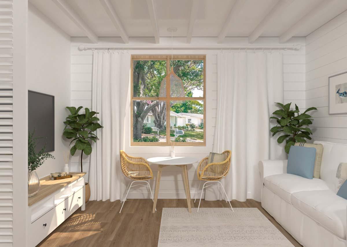 Un petit salon avec un canapé blanc, une télévision, une table et deux fauteuils en rotin