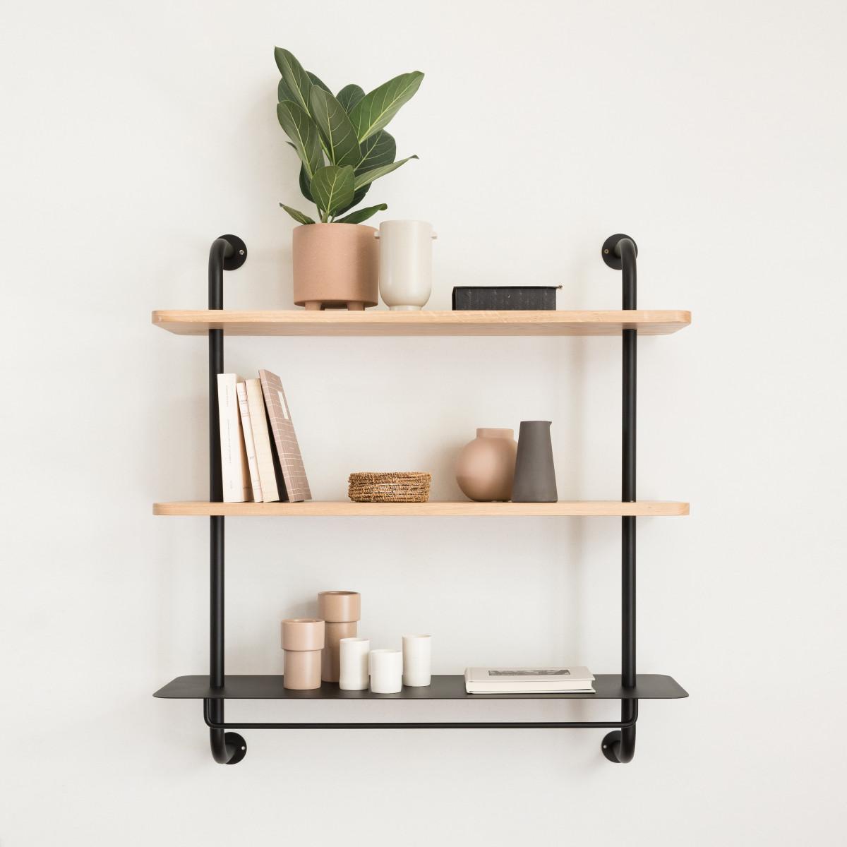 Du tube en métal noir et des planches en bois blond forment des étagères pratiques