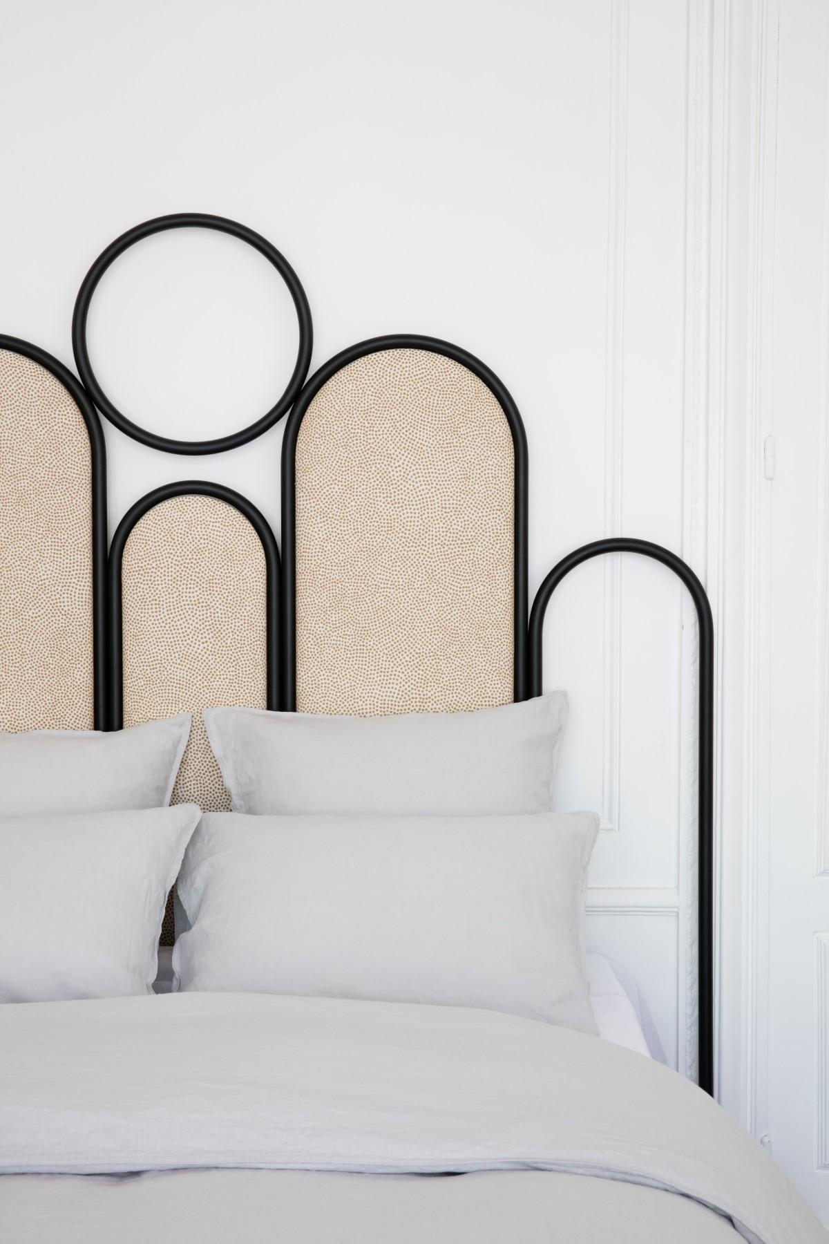 Une tête de lit en tube métallique noir et en liège