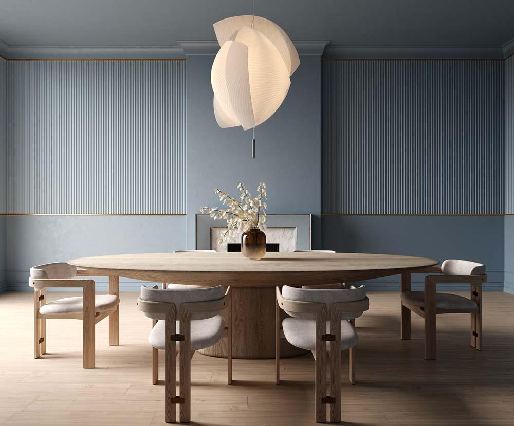 Une salle à manger en teintes sobres avec une grande table ronde en bois clair et des fauteuils assortis