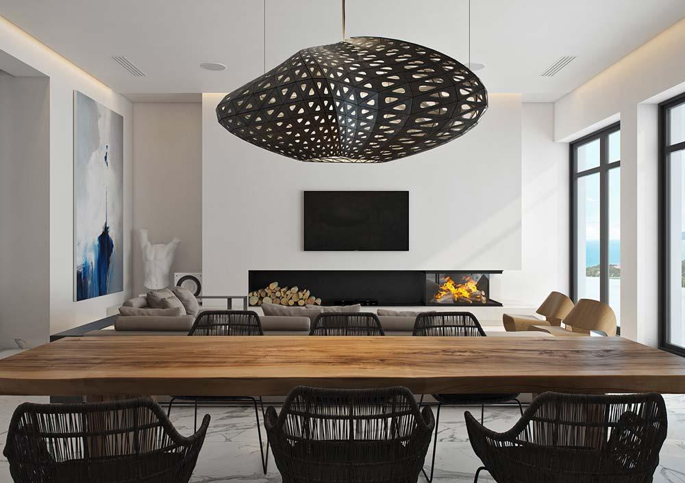 Une salle à manger bord de mer lumineuse avec une grande table en bois, des sièges en osier et un luminaire imitation huître