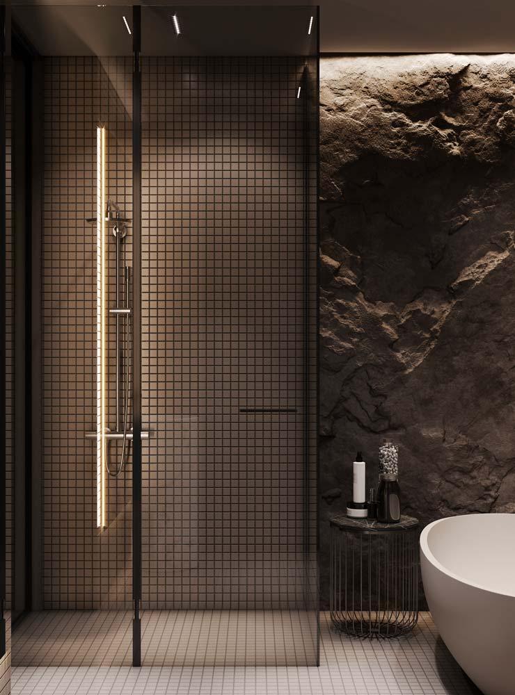 Une salle de bain avec une cabine de douche en carrelage à petits carreaux et un pan de mur en pierre sombre éclairé par des néons blancs