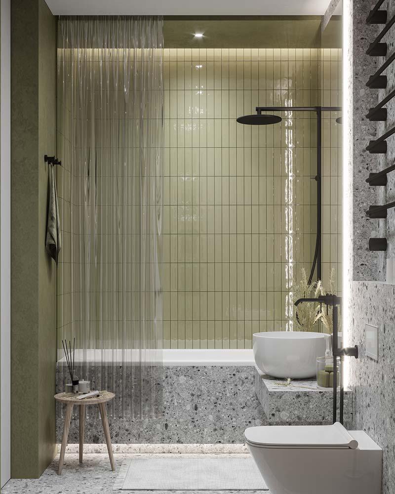 Un mur de baignoire en zellige vert avec une robinetterie noire et du terrazzo gris dans le reste de la salle de bain