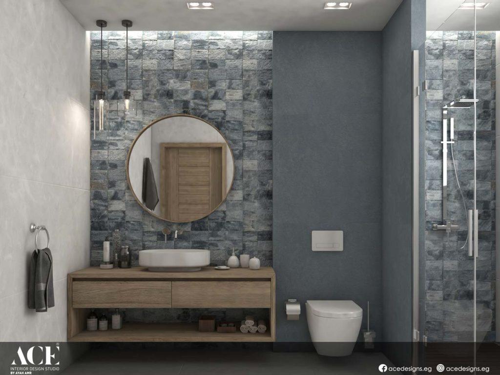 Du zellige carré dans une salle de bain aux teintes grises avec une douche, un miroir rond et un meuble en bois