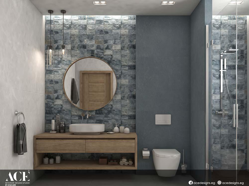 Du zellige gris dans une salle de bain avec une douche, un miroir rond et un meuble en bois