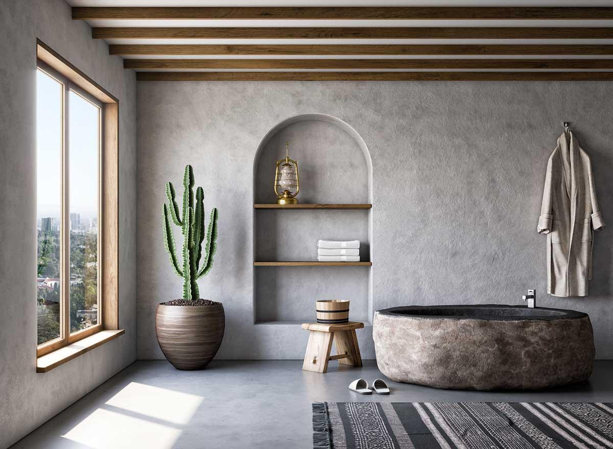 Une salle de bain en tadelakt avec une baignoire ronde en pierre et de la petite déco naturelle en bois