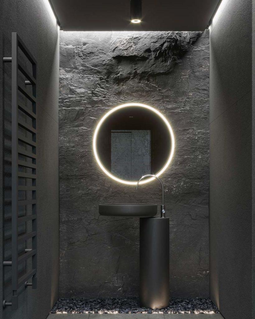 Une salle de bain grise avec un mur en pierre, un chauffage vertical et un petit miroir rond éclairé d'un néon circulaire au-dessus d'un lavabo gris