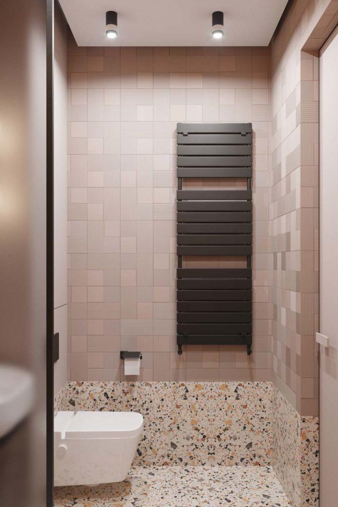 Des murs en zellige carré beige et en terrazzo avec un chauffage noir