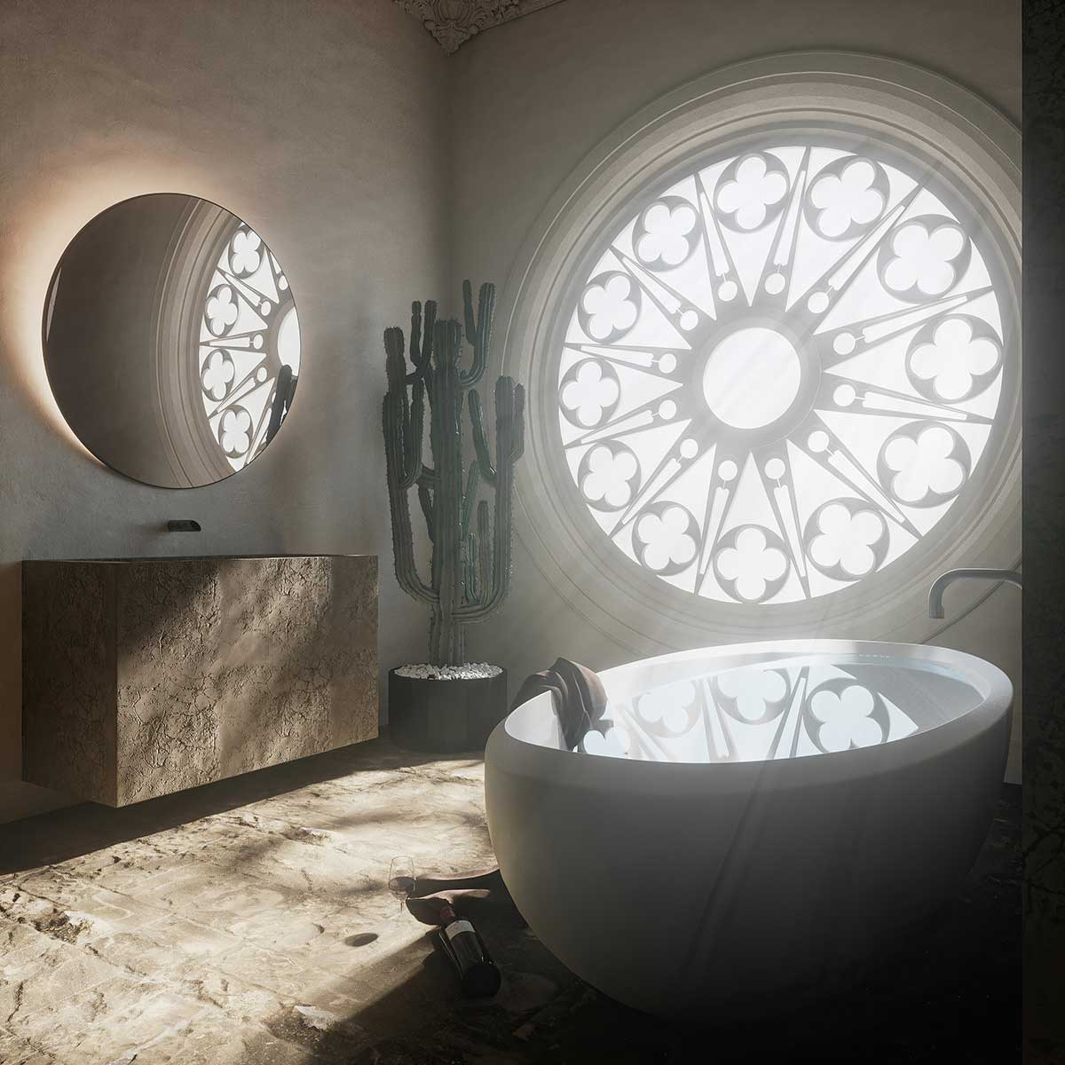 Une petite salle de bain avec une baignoire ronde, un grand vitrail en rosace, un miroir rond et un meuble en pierre