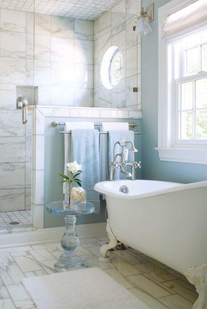 Salle de bain en marbre blanc décoré de touches blue sky avec un mur et des serviettes de bain