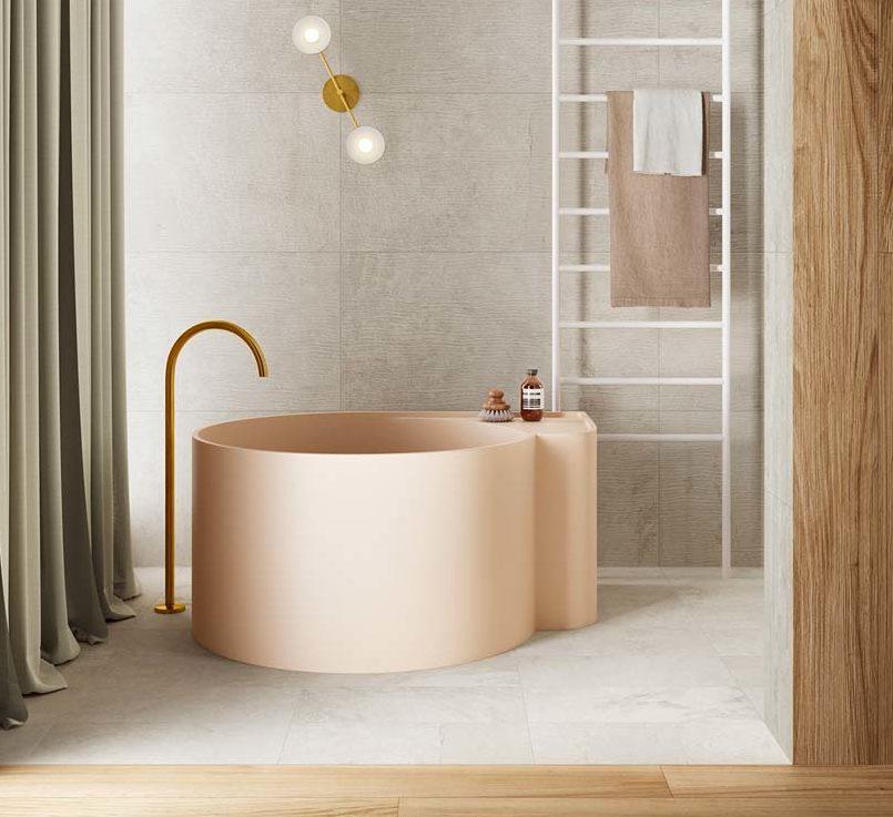 Une salle de bain avec une baignoire ronde rose pâle, du carrelage gris et des planches de bois décoratives