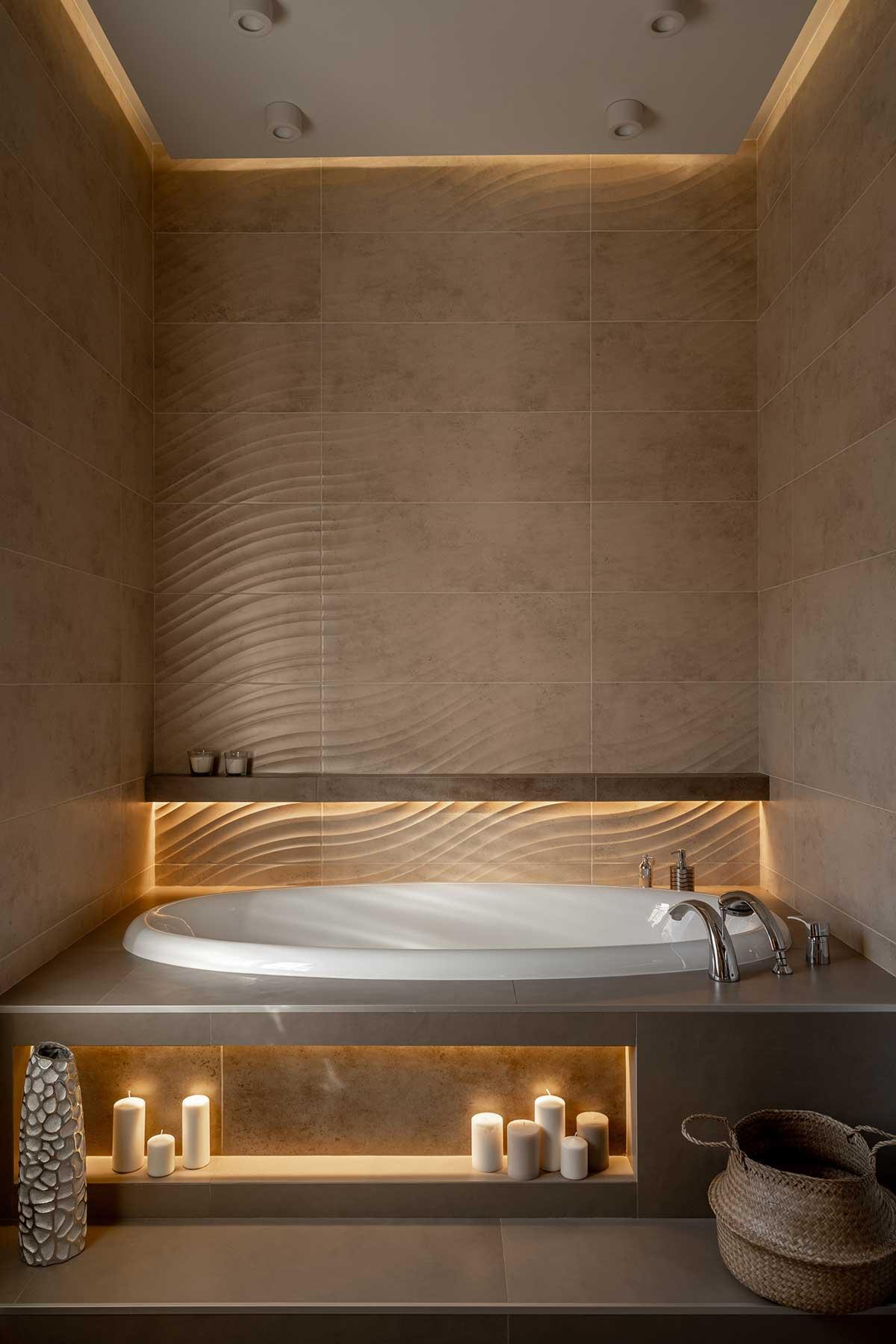 Une salle de bain tendance hamamm avec une grande baignoire ronde, des couleurs sable, des bougies et du carrelage ondulé