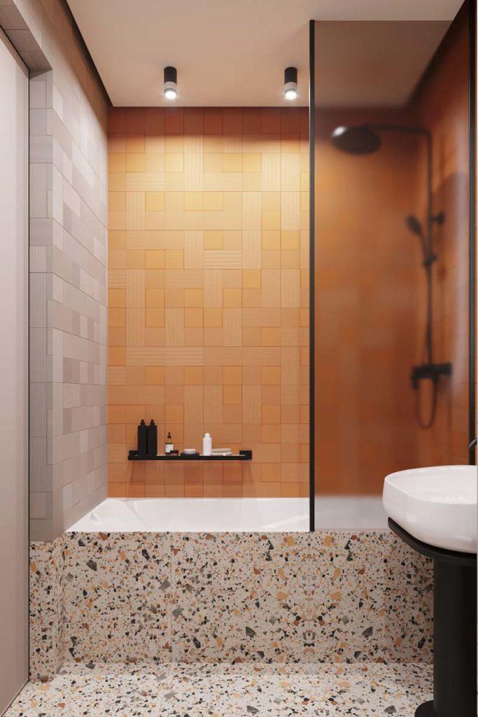 Des murs en zellige orange et gris et un sol en terrazzo dans une salle de bain avec baignoire
